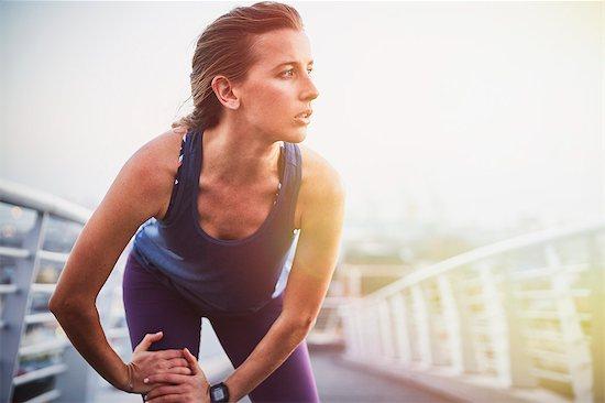 Female runner stretching leg on urban footbridge Stock Photo - Premium Royalty-Free, Image code: 6124-08820833