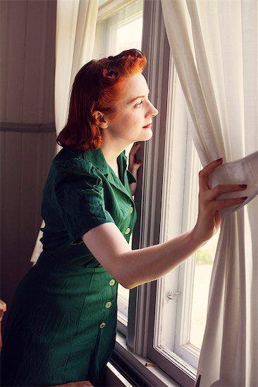 Sweden, Woman looking trough window Stock Photo - Premium Royalty-Free, Image code: 6126-08644023