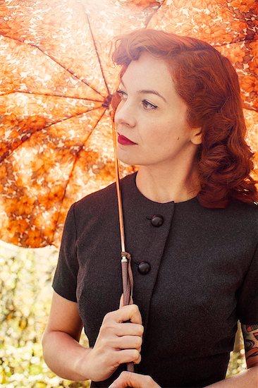 Sweden, Redheaded woman holding umbrella Stock Photo - Premium Royalty-Free, Image code: 6126-08644020