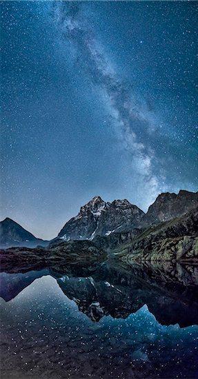 The milky way reflected in Lake Superior near Mount Monviso. Cozian Alps. Piedmont. Italy. Stock Photo - Premium Royalty-Free, Image code: 6129-09058122