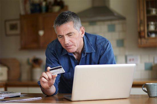 Man holding credit card using laptop in kitchen Stock Photo - Premium Royalty-Free, Image code: 613-07459037