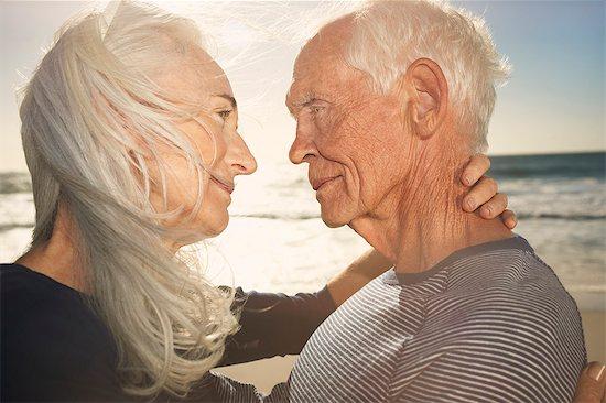 Mature couple embracing at sunset Stock Photo - Premium Royalty-Free, Image code: 613-07734449