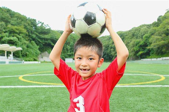 Japanese kid playing soccer Stock Photo - Premium Royalty-Free, Image code: 622-08893862