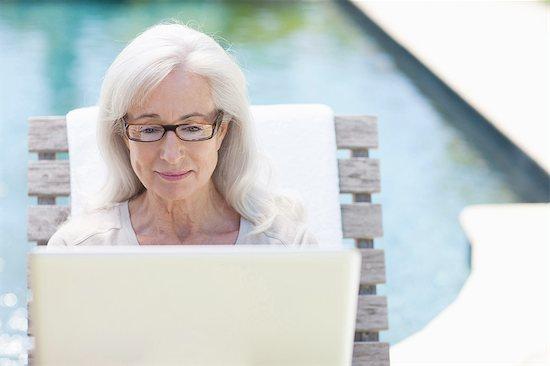 Senior woman using laptop at poolside Stock Photo - Premium Royalty-Free, Image code: 635-07763057