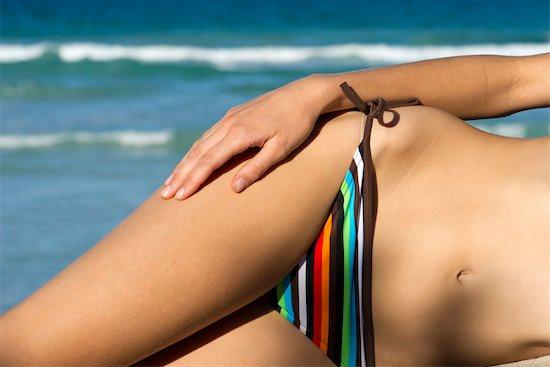 Woman in bikini lying on side, mid section Stock Photo - Premium Royalty-Free, Image code: 632-05760528