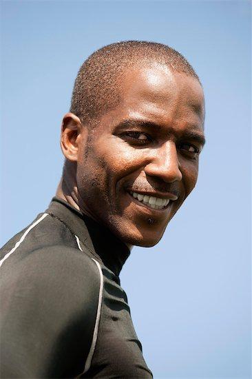 Man smiling over shoulder, portrait Stock Photo - Premium Royalty-Free, Image code: 632-05992016