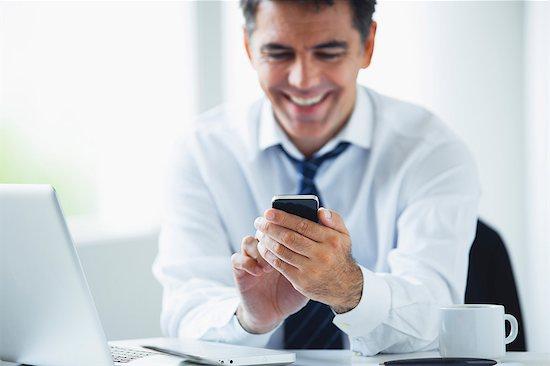 Businessman using smartphone, smiling Stock Photo - Premium Royalty-Free, Image code: 632-06118306