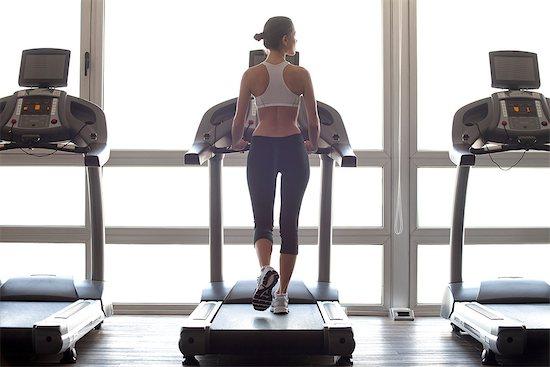 Woman jogging on treadmill at gym Stock Photo - Premium Royalty-Free, Image code: 632-07809482