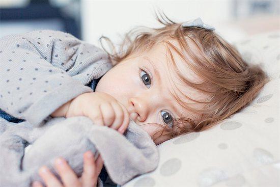 Baby girl lying down, sucking thumb, portrait Stock Photo - Premium Royalty-Free, Image code: 632-07849481