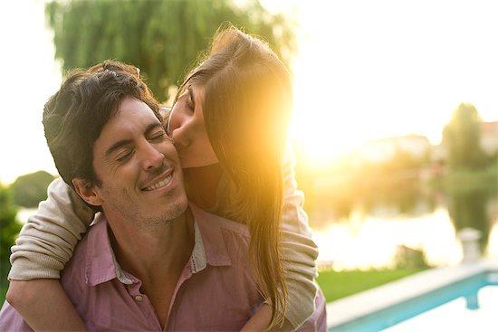 Woman kissing boyfriend on cheek Stock Photo - Premium Royalty-Free, Image code: 632-07849518