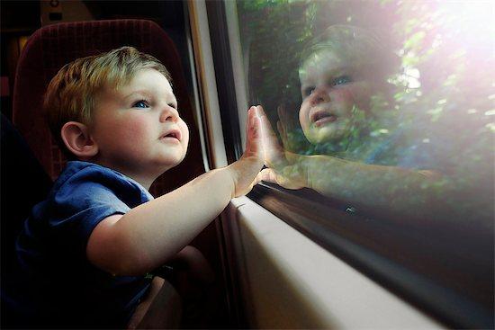 Baby boy gazing out train window in awe Stock Photo - Premium Royalty-Free, Image code: 632-08129902