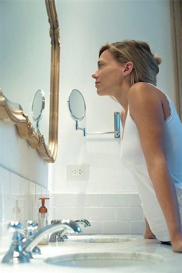 Woman looking at self in bathroom mirror Stock Photo - Premium Royalty-Free, Image code: 632-08331539