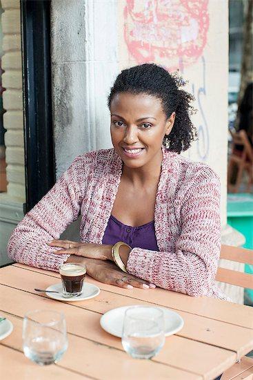 Woman sitting at sidewalk cafe Stock Photo - Premium Royalty-Free, Image code: 632-08331606