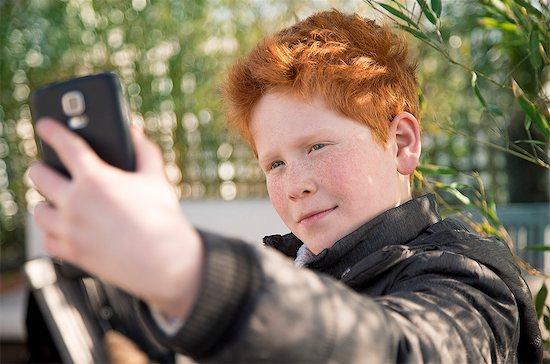Boy using smartphone to take a selfie Stock Photo - Premium Royalty-Free, Image code: 632-08545950