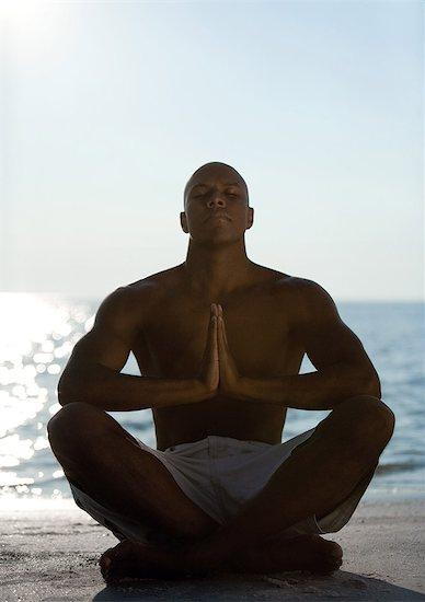 Man sitting in yoga pose on beach, silhouette Stock Photo - Premium Royalty-Free, Image code: 632-01156866