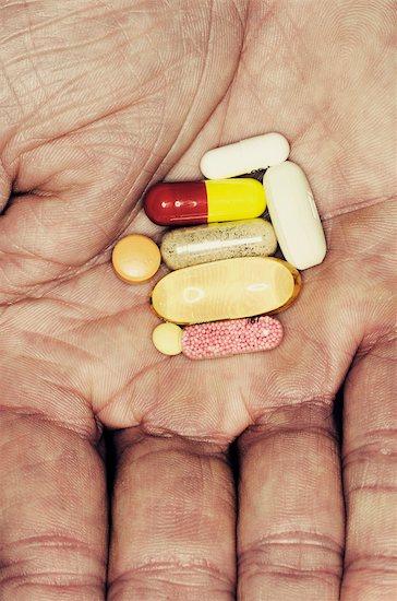 Assorted pills in man's hand Stock Photo - Premium Royalty-Free, Image code: 632-03897968