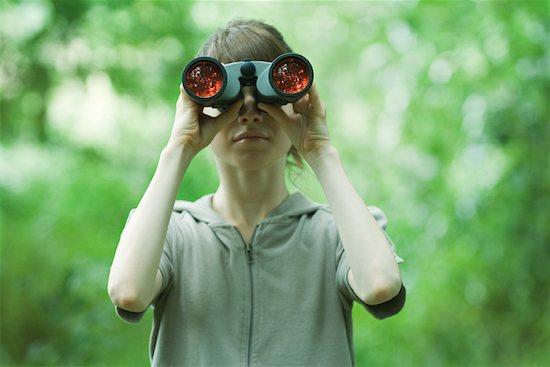 Woman looking through binoculars, front view Stock Photo - Premium Royalty-Free, Image code: 633-01574478