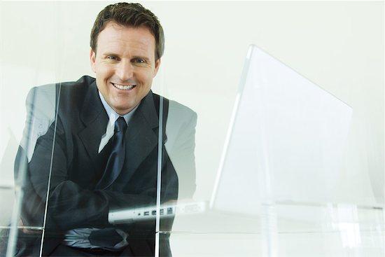 Businessman sitting next to laZSop computer, smiling at camera Stock Photo - Premium Royalty-Free, Image code: 633-01992766