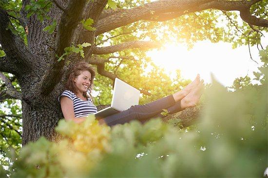 Smiling woman using laptop in tree Stock Photo - Premium Royalty-Free, Image code: 649-06113573