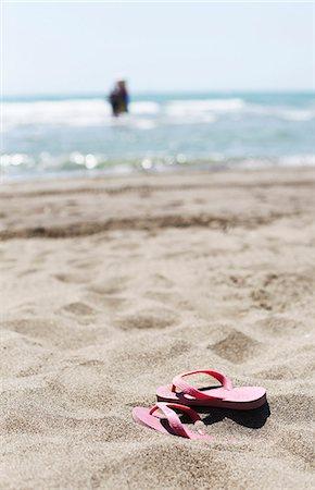 549886717 Flip flops on sandy beach Stock Photo - Premium Royalty-Free