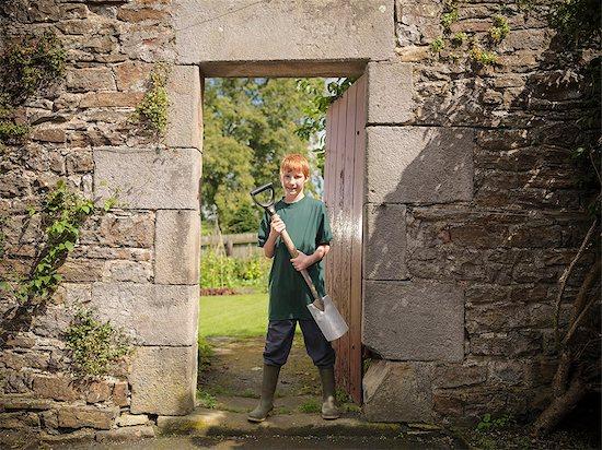 Boy carrying shovel in backyard Stock Photo - Premium Royalty-Free, Image code: 649-06353050