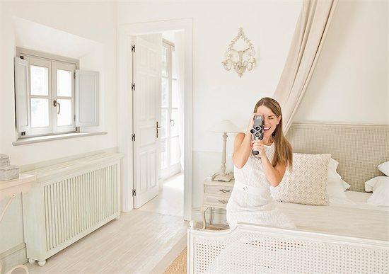 Woman using video camera in bedroom Stock Photo - Premium Royalty-Free, Image code: 649-06353236