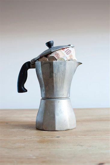 Coffee pot full of money on desk Stock Photo - Premium Royalty-Free, Image code: 649-06717474