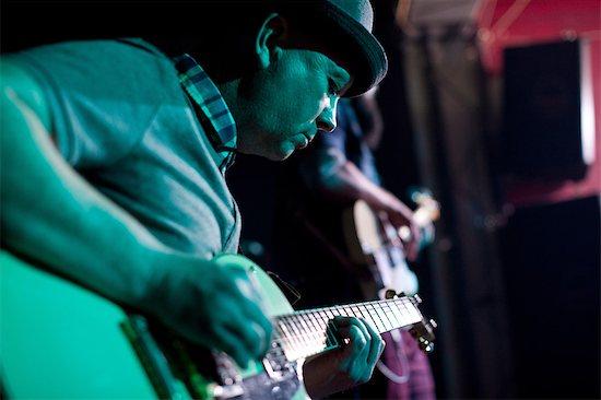 Man playing guitar on stage in nightclub Stock Photo - Premium Royalty-Free, Image code: 649-07063898