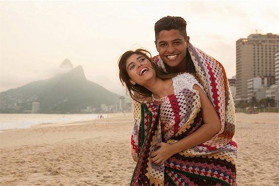 Young couple wrapped in blanket, Ipanema Beach, Rio de Janeiro, Brazil Stock Photo - Premium Royalty-Free, Image code: 649-07119633