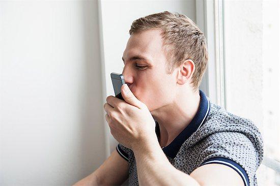 Man kissing mobile phone Stock Photo - Premium Royalty-Free, Image code: 649-07238830