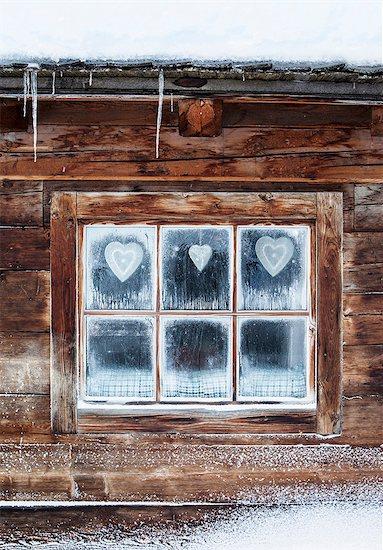 Hearts on window of log cabin, Austrian Alps, Austria Stock Photo - Premium Royalty-Free, Image code: 649-07279754