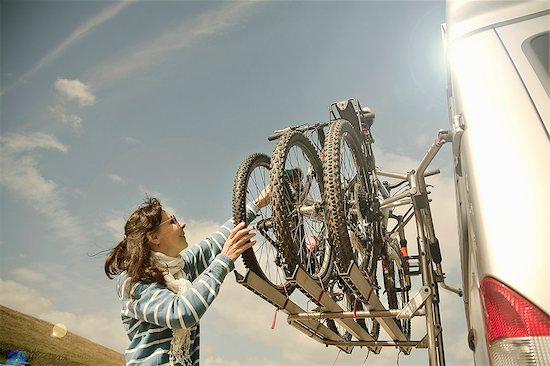 Woman stacking bikes on back of camper van Stock Photo - Premium Royalty-Free, Image code: 649-07585651