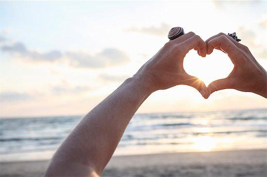 Female hands making heart shape at sunset on beach Stock Photo - Premium Royalty-Free, Image code: 649-07710711