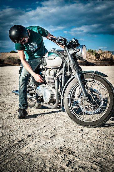 Mid adult man checking motorcycle on arid plain, Cagliari, Sardinia, Italy Stock Photo - Premium Royalty-Free, Image code: 649-07803245
