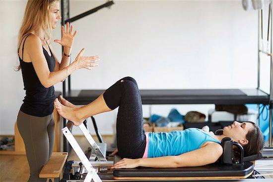 Tutor instructing female student lying on reformer in pilates gym Stock Photo - Premium Royalty-Free, Image code: 649-07905360