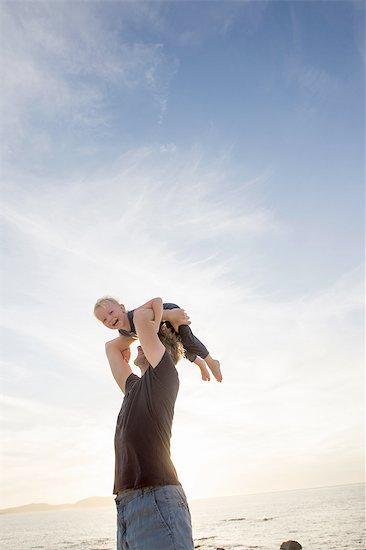 Mature man lifting up his toddler daughter on beach, Calvi, Corsica, France Stock Photo - Premium Royalty-Free, Image code: 649-08328709