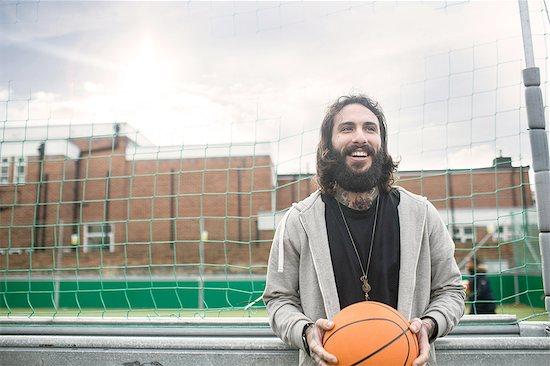 Portrait of mid adult man holding basketball Stock Photo - Premium Royalty-Free, Image code: 649-08422749