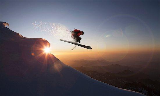 Skier jumping on a snowy slope at sunset, Zermatt, Canton Wallis, Switzerland Stock Photo - Premium Royalty-Free, Image code: 649-08661171
