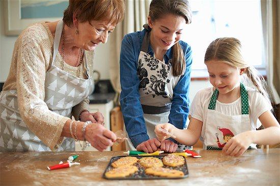 Senior woman and granddaughters decorating Christmas tree cookies Stock Photo - Premium Royalty-Free, Image code: 649-08860522