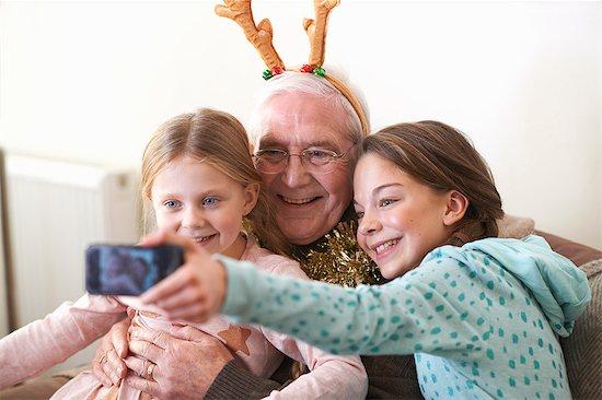 Sisters taking smartphone selfie with grandfather in reindeer antlers Stock Photo - Premium Royalty-Free, Image code: 649-08894382