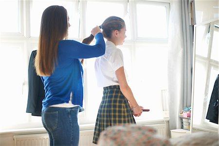 3a12f8b7cf school girl skirt - Mother putting teenage schoolgirl daughter's hair in  ponytail Stock Photo - Premium