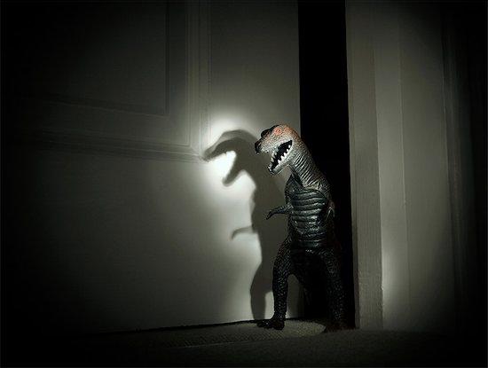 Toy dinosaur spotlit in darkened doorway Stock Photo - Premium Royalty-Free, Image code: 649-09026277