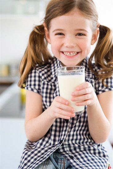 Girl smiling at camera holding glass Stock Photo - Premium Royalty-Free, Image code: 649-02053938