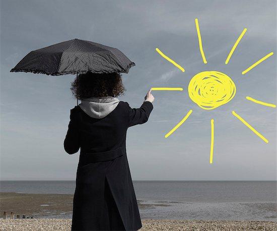 Woman painting sun onto grey sky Stock Photo - Premium Royalty-Free, Image code: 649-03009491