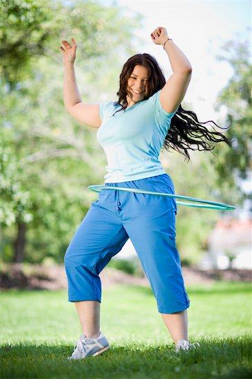 young plump girl doing hula hoop Stock Photo - Premium Royalty-Free, Image code: 649-03291705