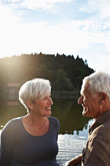 Senior couple sitting at jetty Stock Photo - Premium Royalty-Free, Image code: 649-03769271
