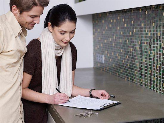Couple signs tenancy agreement Stock Photo - Premium Royalty-Free, Image code: 649-03775260