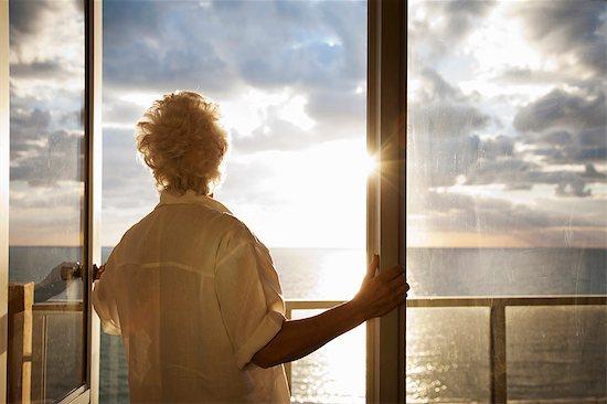 Senior Woman watching sunrise Stock Photo - Premium Royalty-Free, Image code: 649-03816888
