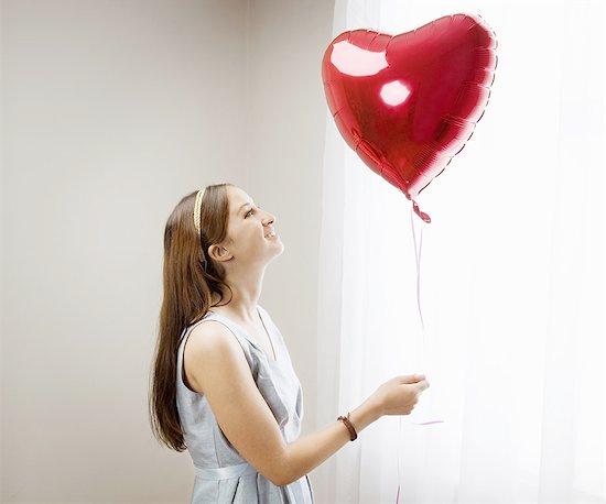 Woman looking at heart shaped balloon Stock Photo - Premium Royalty-Free, Image code: 649-03817211