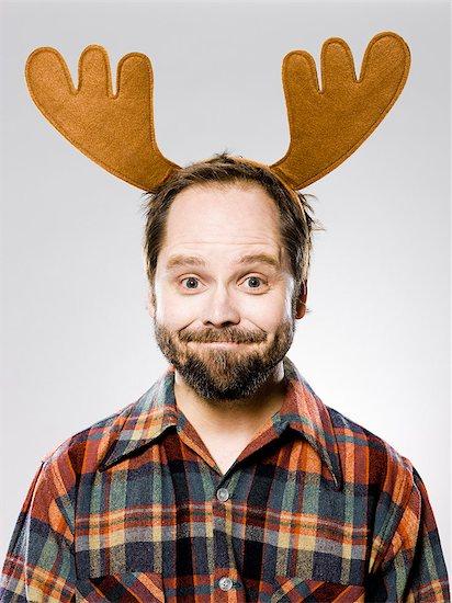 man in a plaid shirt wearing antlers Stock Photo - Premium Royalty-Free, Image code: 640-06051693